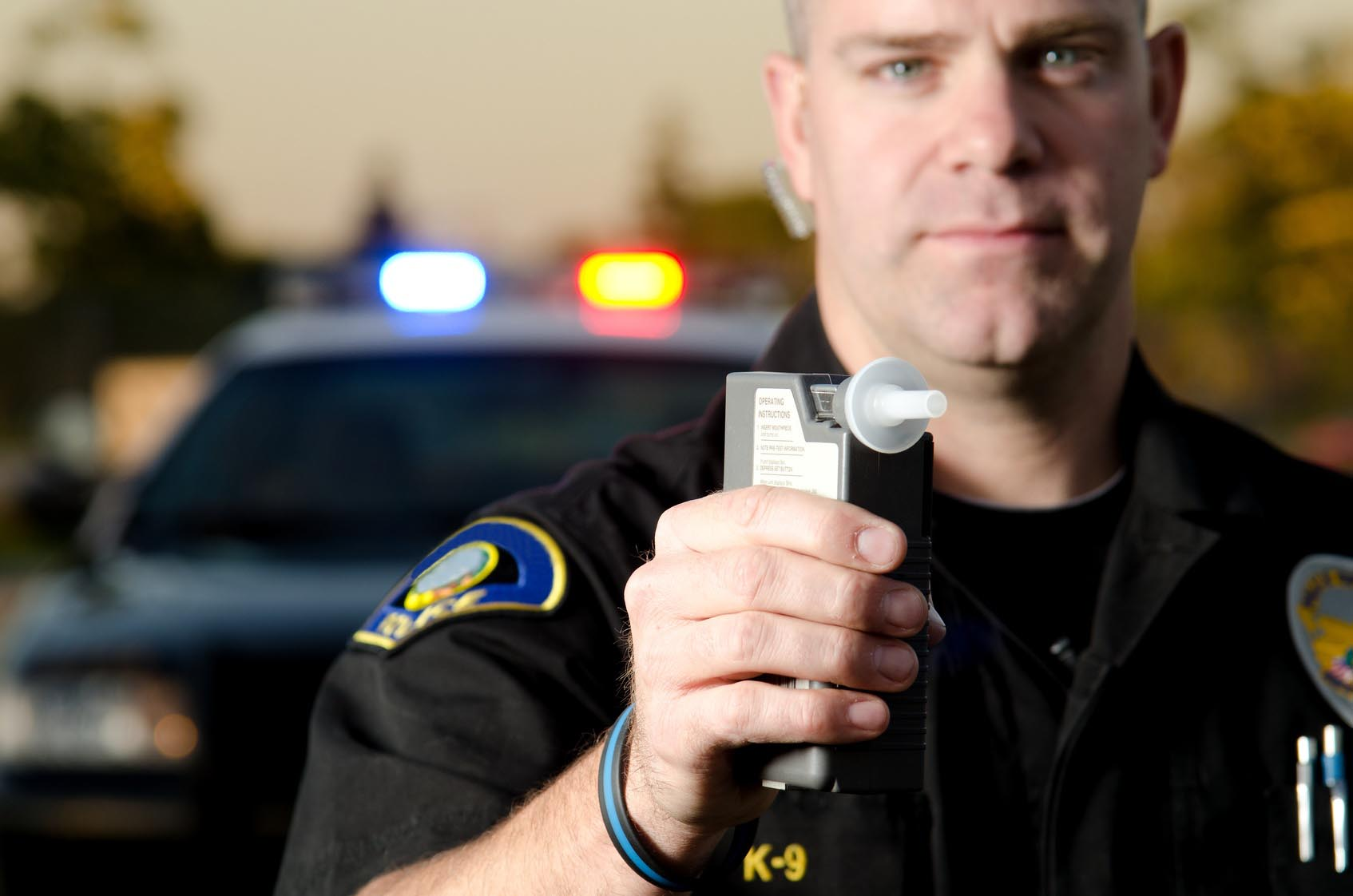 Police office holding an alcohol breath analyzer.